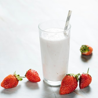 Szkło z mlekiem i stawberries na prostym tle