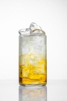 Szkło z sokiem i lodem na białym tle.
