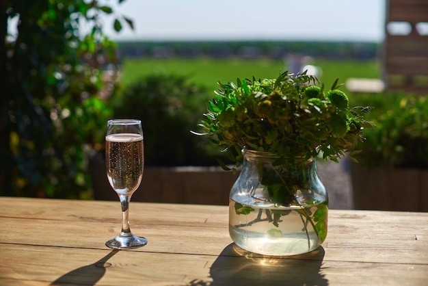 Szkło z szampanem na drewnianym stole, słoneczny dzień.
