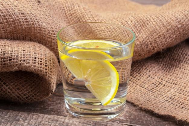 Szkło z wodą i cytryną na drewnianym stole