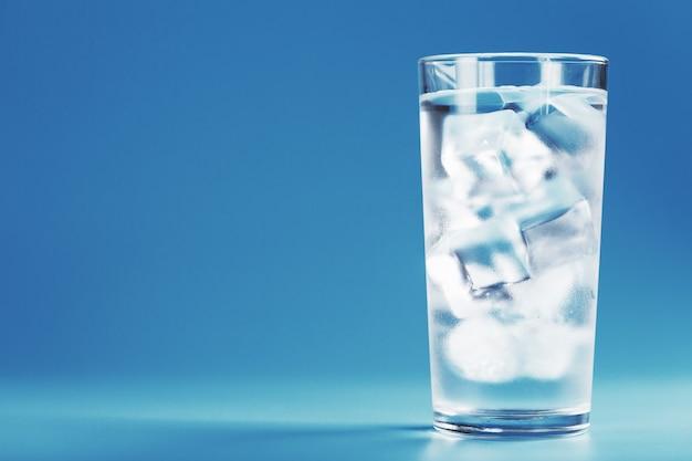Szkło z wodą i kostkami lodu na niebieskim tle. koncepcja ratunkowa w upalny, duszny dzień. wolna przestrzeń