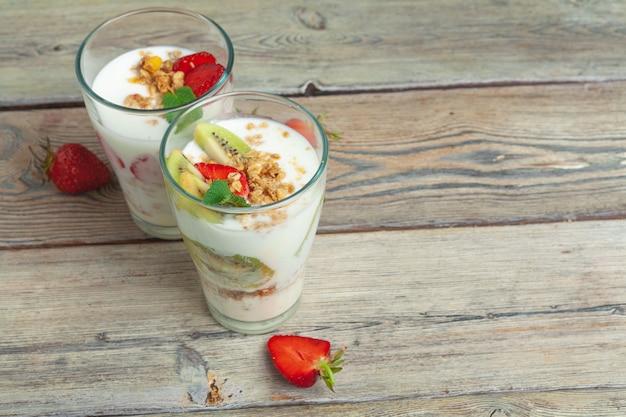 Szkło zdrowy truskawkowy jogurt z świeżymi jagodami na drewnianym stołowym odgórnym widoku