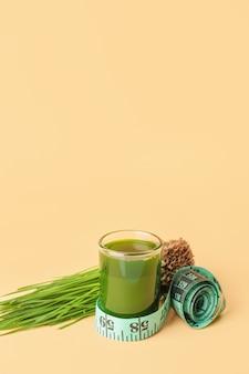Szkło ze świeżym sokiem z trawy pszenicznej i miarką
