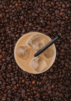 Szkło zimnej kawy z kostkami lodu i słomą na tle świeżych surowych ziaren kawy. widok z góry
