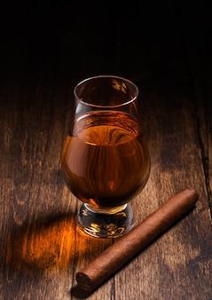 Szkocka whisky single malt w szkle glencairn z kubańskim cygarem na drewnianym stole. widok z góry