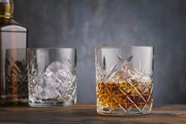 Szkocka whisky w szkle z kostkami lodu na ścianie pustej szklanki
