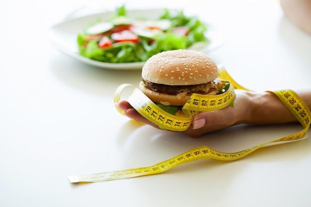 Szkodliwe jedzenie, tłusty burger obok żółtej miarki.