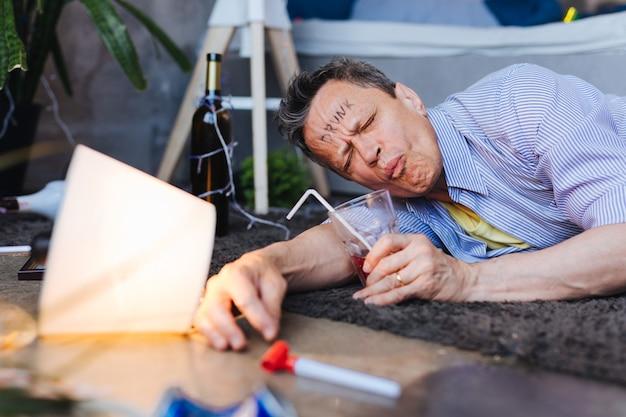 Szkodliwe picie. zmęczony dojrzały mężczyzna lokalizujący na podłodze i połykający koktajl