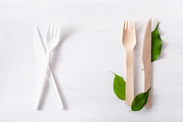 Szkodliwe plastikowe sztućce i przyjazne dla środowiska drewniane sztućce. koncepcja bez plastiku