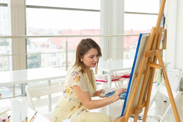 Szkoła artystyczna, koncepcja kreatywności i rozrywki - studentka lub młoda artystka ze sztalugami, paletą i pędzlem malującym obraz w studio.