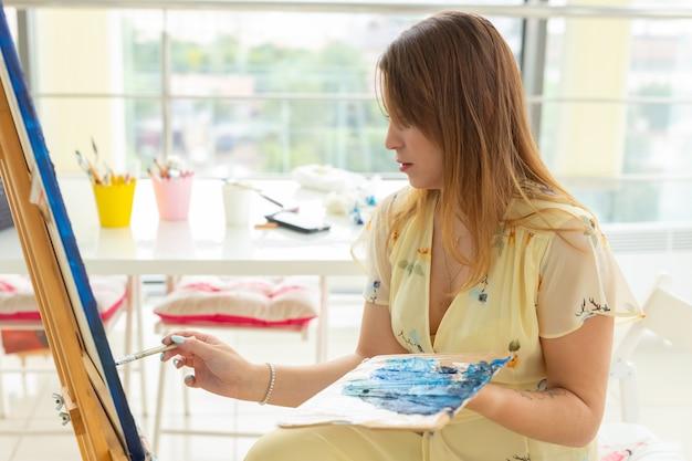Szkoła artystyczna, koncepcja kreatywności i wypoczynku - studentka lub młoda artystka ze sztalugą, paletą