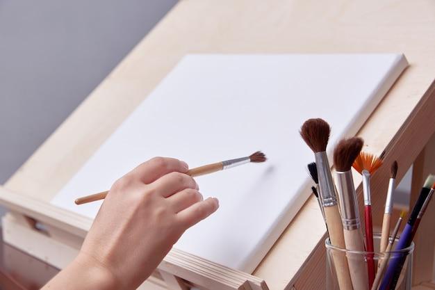 Szkoła artystyczna, ręka artysty w pobliżu obrazu. szczotka z bliska.