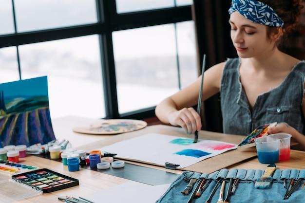 Szkoła artystyczna. zainspirowana młoda artystka malująca krajobraz w nowoczesnym studio. rozmycie okna.