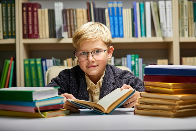 Szkoła chłopiec siedzi przy stole i wykonuje zadania szkolne w otoczeniu stosów książek, edukacji i koncepcji szkoły