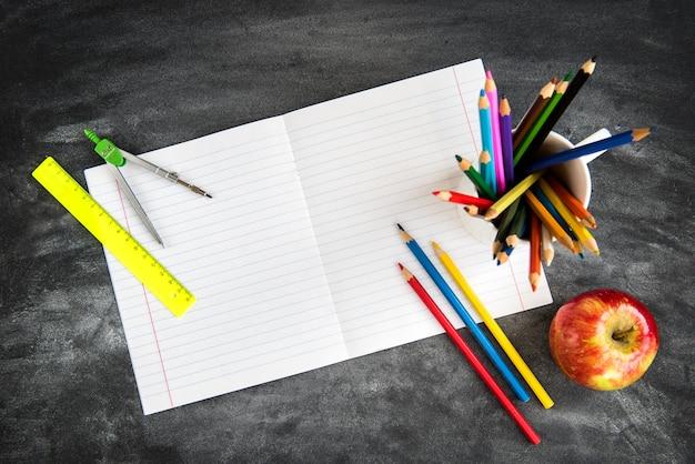 Szkoła dostarcza na tle czarnej tablicy. kredki, kalkulator, zasady i zeszyty. powrót do koncepcji szkoły.
