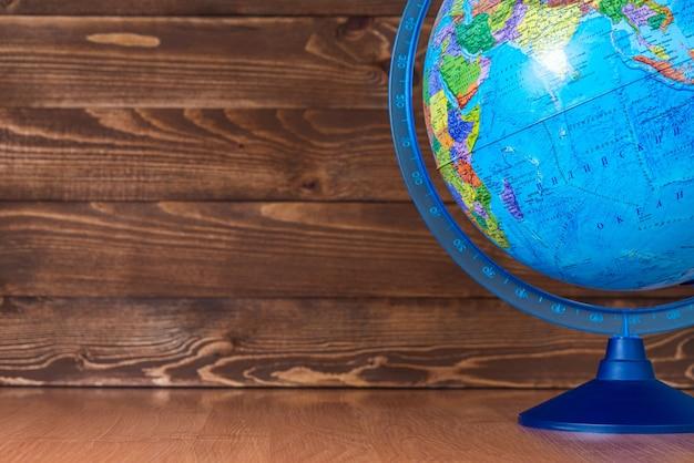 Szkoła drewniana z kulą ziemską i miejscem na tekst.