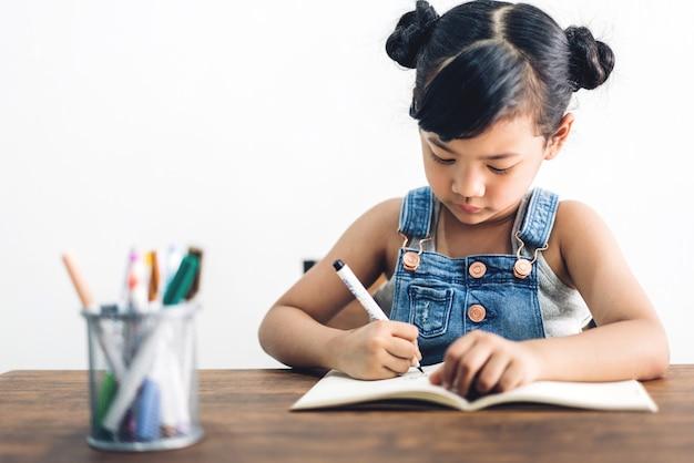 Szkoła dziecko dziewczynka nauka i pisanie w zeszycie z ołówkiem, odrabianie lekcji w domu. koncepcja edukacji