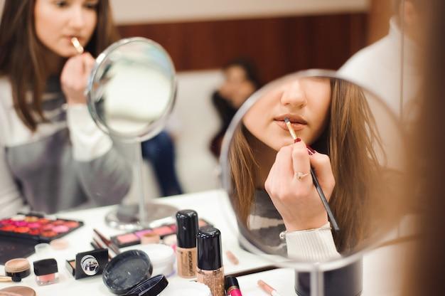 Szkoła makijażu. wizażystka robi profesjonalny makijaż młodej kobiety.