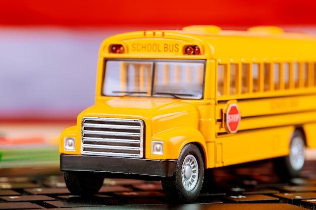 Szkoła online zdalnego uczenia się z żółtym autobusem szkolnym na komputerze z klawiaturą laptopa