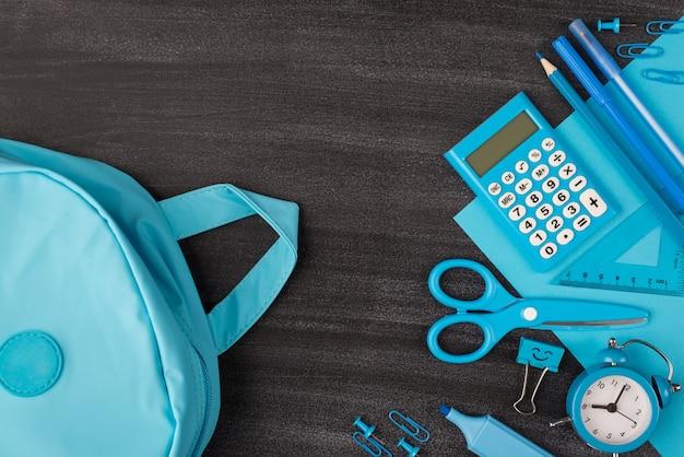 Szkoła papeterii dla koncepcji chłopców. widok z góry na zdjęcie niebieskiej papeterii i plecaka na tablicy z copyspace