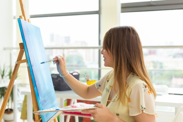 Szkoła plastyczna, kolegium plastyczne, edukacja dla grupy młodych studentów. szczęśliwa młoda kobieta uśmiechnięta, dziewczyna uczy się malować.