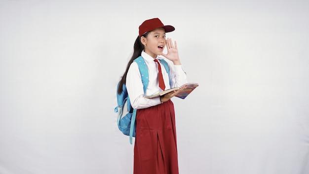 Szkoła podstawowa mała dziewczynka krzyczy w bok na białym tle