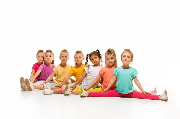 Szkoła tańca dla dzieci, balet, hiphop, tancerze ulicy, funky i nowoczesne na tle białego studia. dziewczyna pokazuje element aerobiku i tańca. nastolatek w stylu hip hop