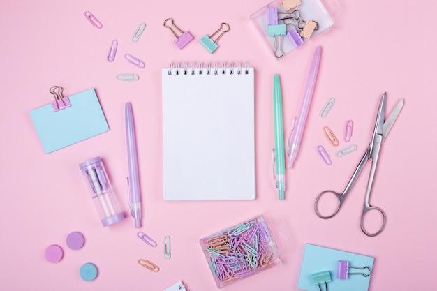 Szkoła tła z notesu i pastelowe kolorowe akcesoria badania na różowym tle powrót do koncepcji szkoły