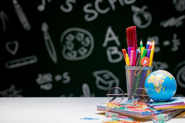 Szkoła tło z akcesoriami papierniczymi. książki, kula ziemska, ołówki i różne artykuły biurowe leżące na biurku na zielonym tle tablicy.