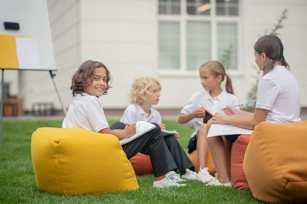 Szkoła. uczniowie siedzą razem na torbach i przygotowują pracę domową