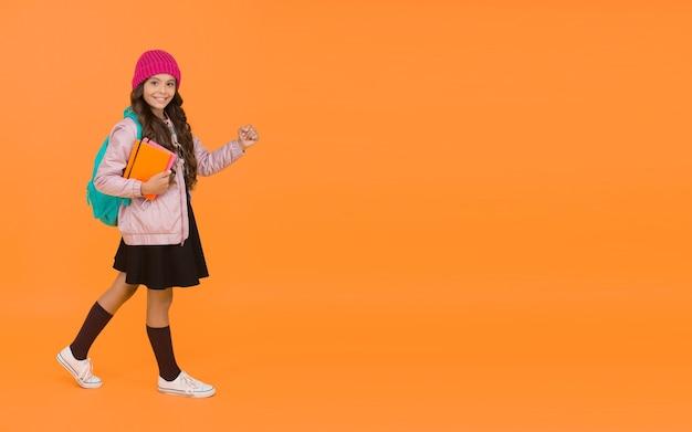 Szkoła wróciła. szczęśliwe małe dziecko z powrotem do szkoły. mała dziewczynka iść do szkoły pomarańczowym tle. powrót do klasy. 1 września. witamy ponownie jesienią, skopiuj przestrzeń.
