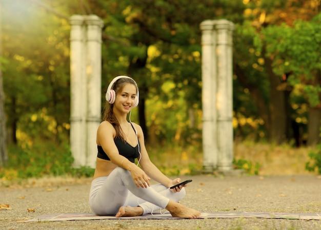 Szkolenia i rekreacja na świeżym powietrzu. młoda sportowa kobieta słucha muzyki w słuchawkach siedząc na macie do jogi w parku w jasny słoneczny dzień