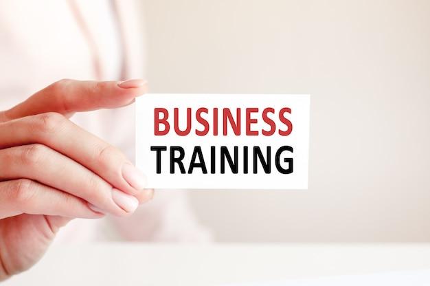 Szkolenie biznesowe jest napisane na białej wizytówce w kobiecej dłoni. różowe tło.