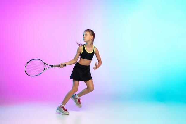 Szkolenie. mała tenisistka w czarnej odzieży sportowej odizolowana na ścianie gradientowej