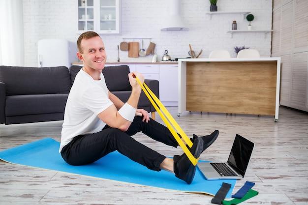 Szkolenie online. człowiek robi ćwiczenia z gumkami w domu, wolna przestrzeń. uprawianie sportu w domu