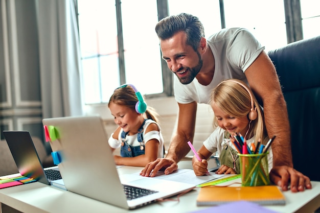 Szkolenie online. dwie siostry uczennice w słuchawkach słuchają lekcji na laptopach. tata pomaga córkom w nauce. szkoła w domu w pandemii i kwarantannie.