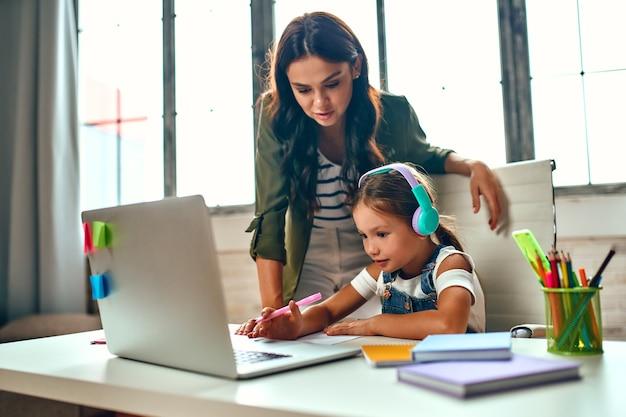 Szkolenie online. mama pomaga córce w lekcjach. uczennica w słuchawkach słucha lekcji na laptopie. szkoła w domu w pandemii i kwarantannie.