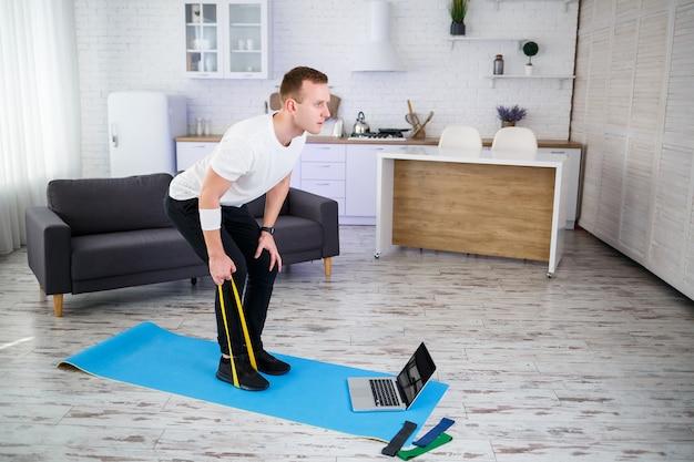Szkolenie online. młody człowiek robi ćwiczenia z gumkami fitness z samouczkiem online w domu, wolna przestrzeń. uprawianie sportu w domu