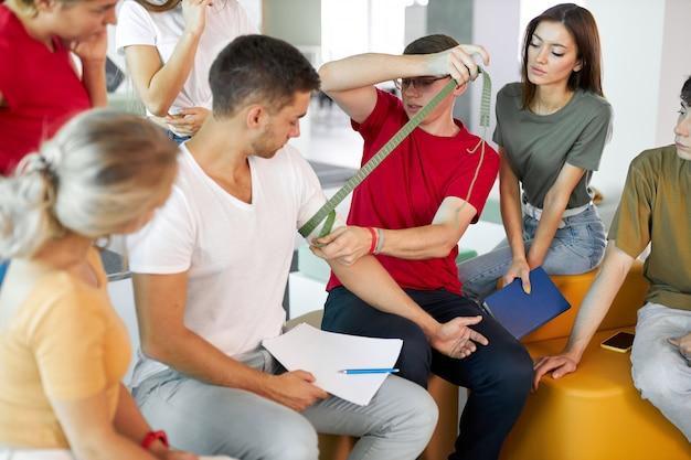 Szkolenie pierwszej pomocy w sali wykładowej, uczenie się szynowania ramienia poszkodowanego pacjenta bandażem