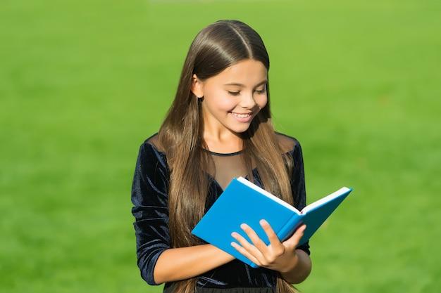 Szkolenie to podstawa na przyszłość. szczęśliwe dziecko czytać książki zielona trawa. powrót do szkoły. 1 września. formalne kształcenie. dzień wiedzy. nauczanie prywatne. lekcja prywatna.