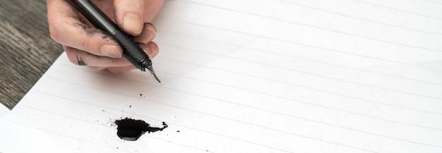 Szkolenie z kaligrafii. wieczne pióro w dłoniach poplamionych atramentem.