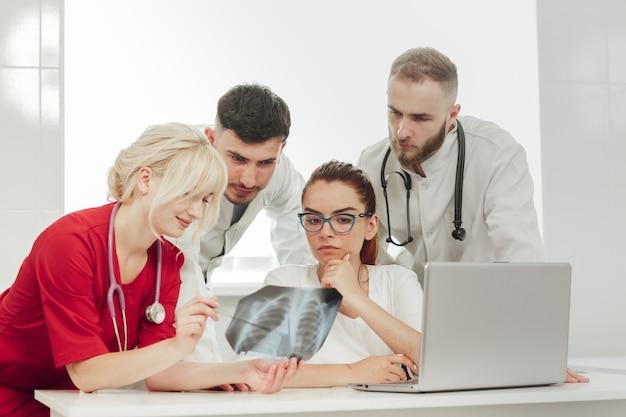 Szkolenie ze stażystami. młody lekarz o blond włosach prowadzi w gabinecie wykład dla młodych stażystów, omawiając zdjęcie rentgenowskie. medycyna, edukacja.