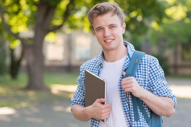 Szkolna chłopiec z książką w parku