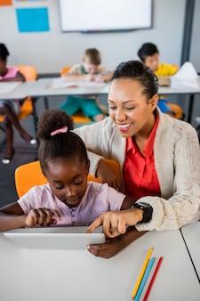 Szkolna dziewczyna używa pastylkę przy biurkiem z jej nauczycielem