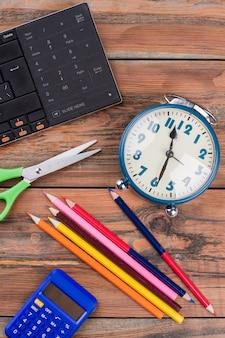Szkolne akcesoria do prac domowych na brązowym drewnianym stole. nożyczki z kalkulatorem i budzikiem. widok z góry na płasko.