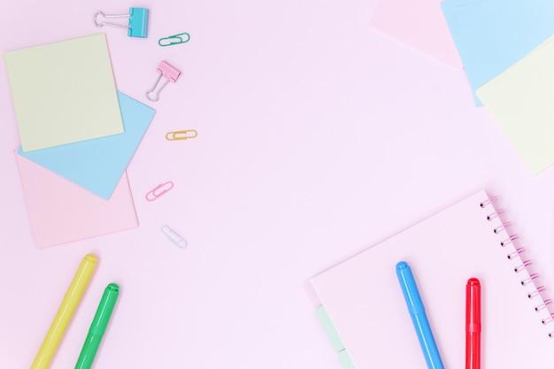 Szkolne biurko z kolorowymi papeteriami na różowym tle.