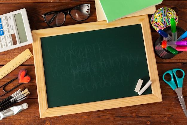 Szkolne dostawy na drewnianym stole i tablicy