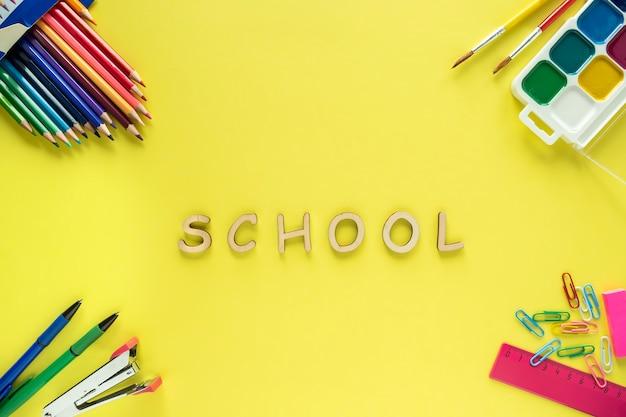 Szkolne dostawy na żółtym tle. koncepcja szkoły. powrót do szkoły