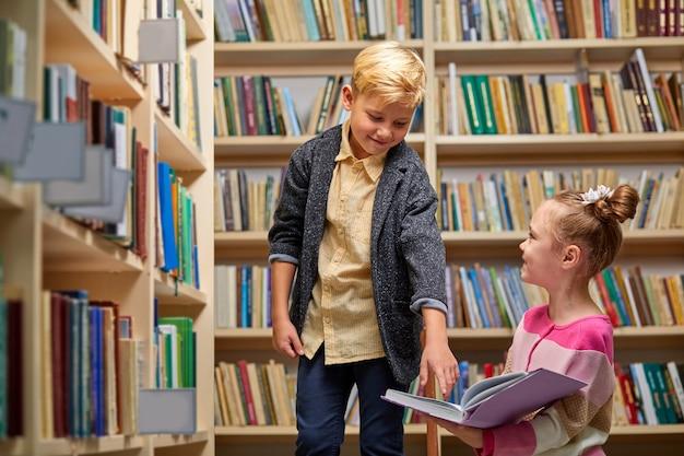 Szkolne dzieci przygotowujące się do lekcji w szkolnej bibliotece, wspólne czytanie podręczników i omawianie, koncepcja edukacji