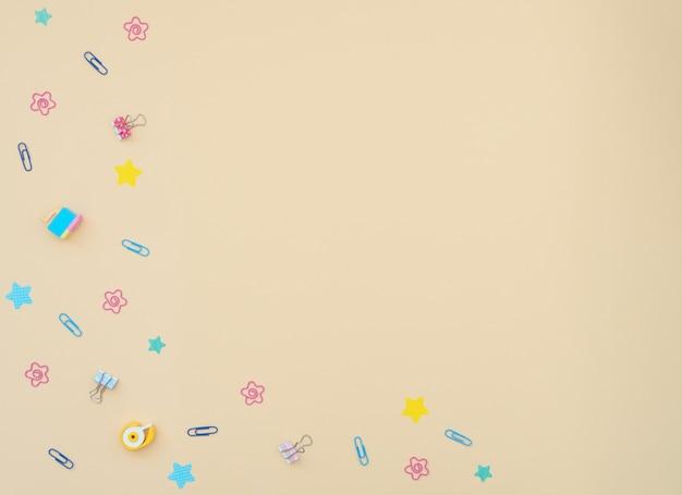Szkolne i biurowe klipsy, papier listowy, naklejki, gumki na żółtym tle